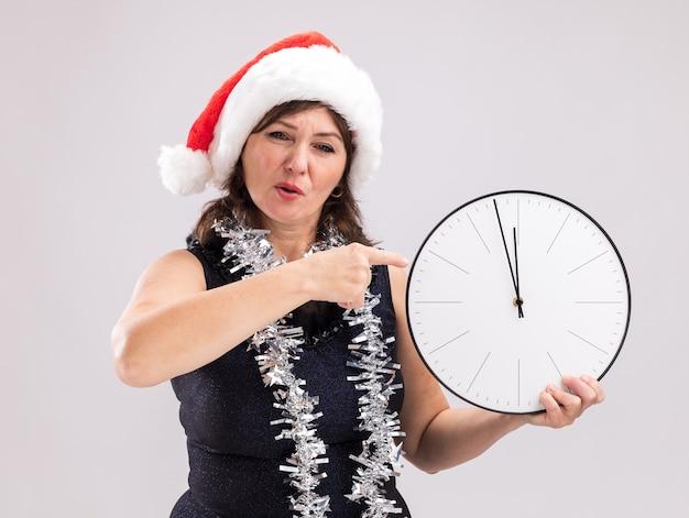Mulher de meia-idade ansiosa com chapéu de papai noel e guirlanda de ouropel no pescoço segurando e apontando para o relógio, olhando para a câmera isolada no fundo branco