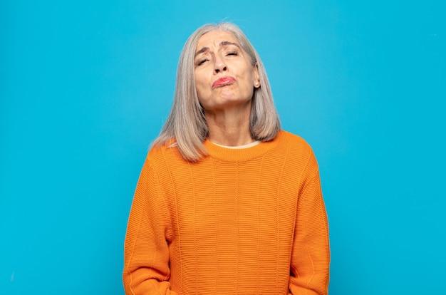 Mulher de meia-idade apertando os lábios com uma expressão fofa, divertida, feliz e adorável, mandando um beijo