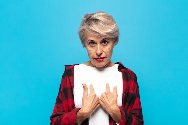 Mulher de meia-idade apontando para si mesma com um olhar confuso e curioso, chocada e surpresa por ser escolhida