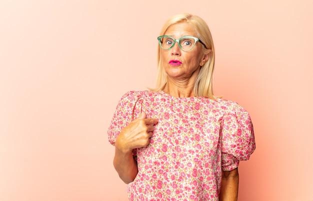 Mulher de meia idade apontando para si mesma