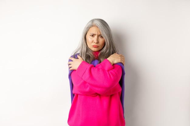 Mulher de meia-idade asiática defensiva e ofendida abraçando o corpo, se confortando e olhando com raiva para a câmera, franzindo a testa, insultada, em pé sobre um fundo branco.