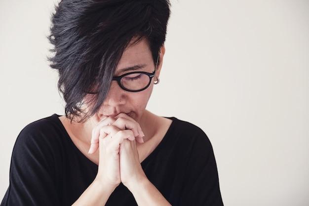 Mulher de meia idade asiática usar óculos rezando com as mãos juntas de manhã sobre parede branca