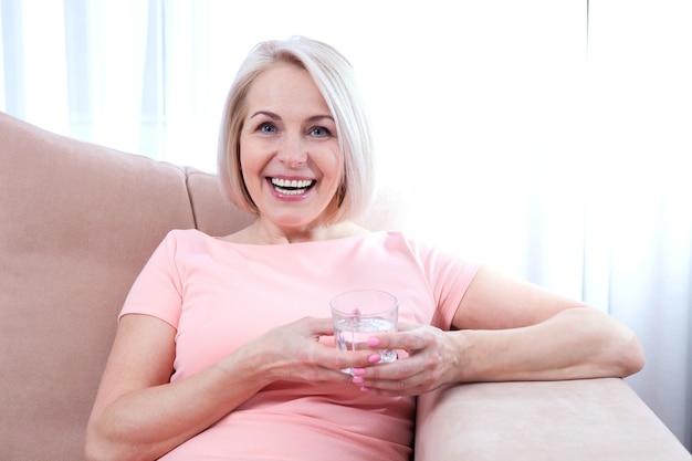 Mulher de meia-idade bebendo água em casa