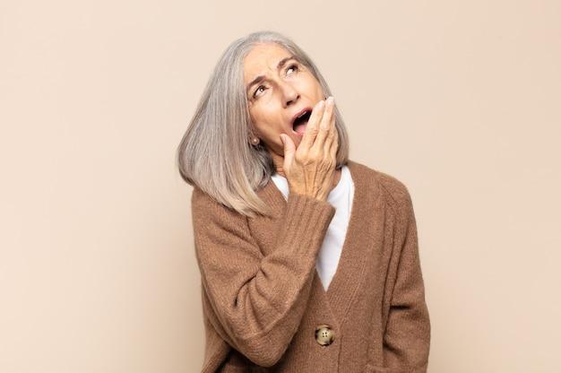 Mulher de meia-idade bocejando preguiçosamente no início da manhã, acordando e parecendo sonolenta, cansada e entediada