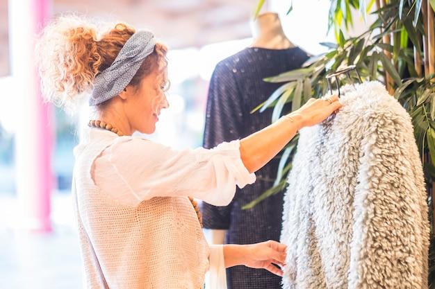 Mulher de meia-idade bonita e cacheada dentro de uma loja de roupas procurando casacos de pele sintética para a nova temporada de moda de inverno para comprar e usar ou fazer um presente para um amigo - conceito de comércio