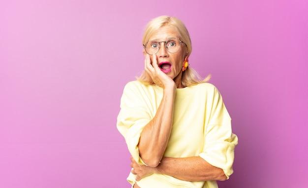 Mulher de meia-idade boquiaberta em choque e descrença, com a mão na bochecha e os braços cruzados, sentindo-se estupefata e surpresa