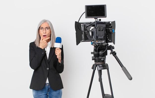 Mulher de meia idade, cabelo branco, boca e olhos bem abertos, mão no queixo e segurando um microfone