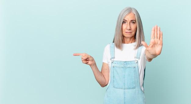 Mulher de meia-idade, cabelo branco com cara de sério, mostrando a palma da mão aberta fazendo um gesto de parada e apontando para o lado