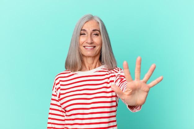 Mulher de meia-idade, cabelos brancos, sorrindo e parecendo amigável, mostrando o número cinco