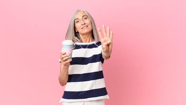 Mulher de meia-idade, cabelos brancos sorrindo e parecendo amistosa, mostrando o número quatro e segurando uma lata de café para viagem