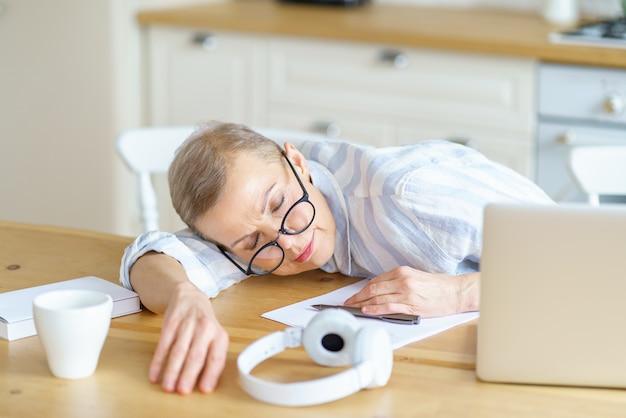 Mulher de meia-idade cansada de óculos dormindo na mesa de madeira da cozinha enquanto trabalha ou
