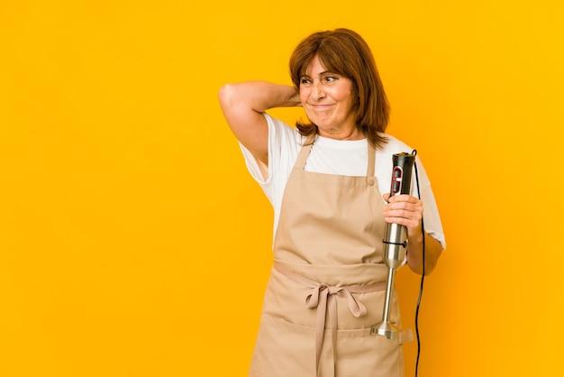 Mulher de meia idade, caucasiano, cozinheiro, segurando um mixer isolado, tocando a parte de trás da cabeça, pensando e fazendo uma escolha.