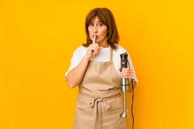 Mulher de meia-idade, caucasiano, cozinheiro, segurando uma batedeira isolada, mantendo um segredo ou pedindo silêncio.