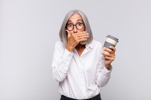 Mulher de meia-idade cobrindo a boca com as mãos com uma expressão chocada e surpresa, mantendo um segredo ou dizendo oops café conceito