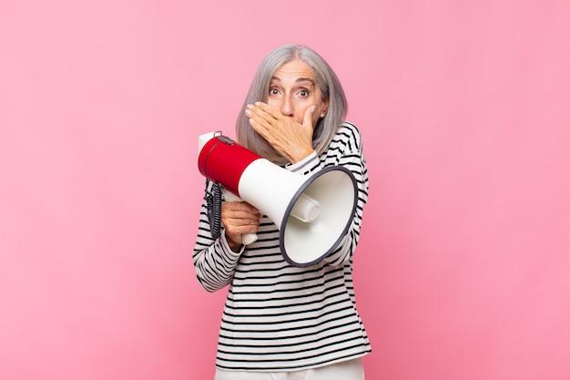Mulher de meia-idade cobrindo a boca com as mãos com uma expressão chocada e surpresa, mantendo um segredo ou dizendo oops com um megafone