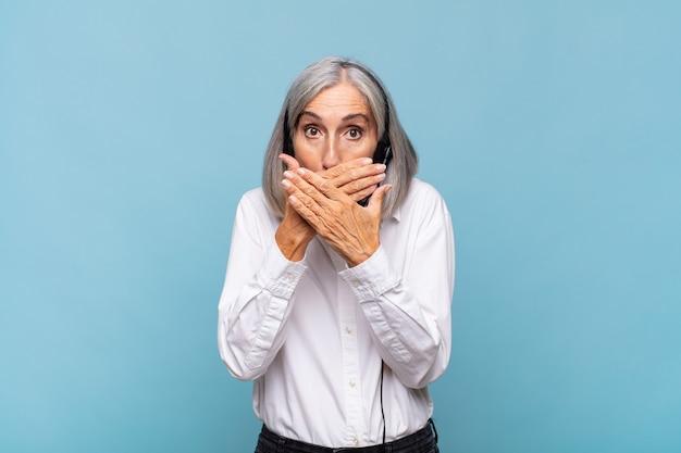 Mulher de meia-idade cobrindo a boca com as mãos com uma expressão chocada e surpresa, mantendo um segredo ou dizendo oops. conceito de telemarketing