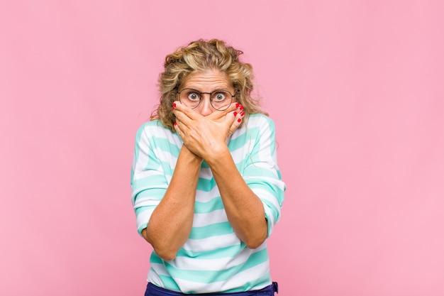 Mulher de meia-idade cobrindo a boca com as mãos com uma expressão chocada e surpresa, mantendo um segredo ou dizendo oops