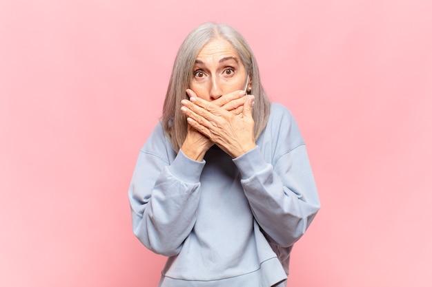 Mulher de meia-idade cobrindo a boca com as mãos com uma expressão chocada e surpresa, mantendo um segredo ou dizendo oops Foto Premium