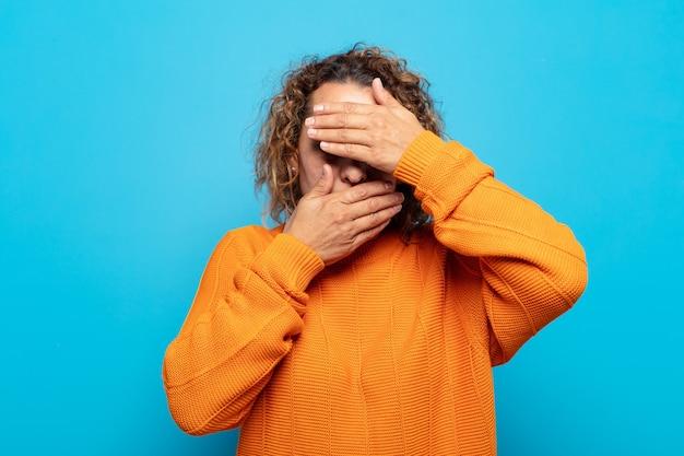 Mulher de meia-idade cobrindo o rosto com as duas mãos dizendo não! recusando fotos ou proibindo fotos