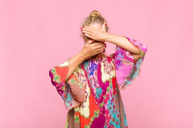 Mulher de meia idade cobrindo o rosto com as duas mãos e dizendo não! recusando fotos ou proibindo fotos