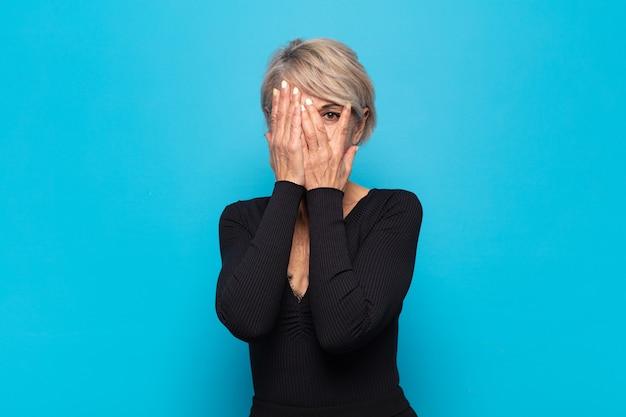 Mulher de meia-idade cobrindo o rosto com as mãos, espiando por entre os dedos com expressão de surpresa e olhando para o lado