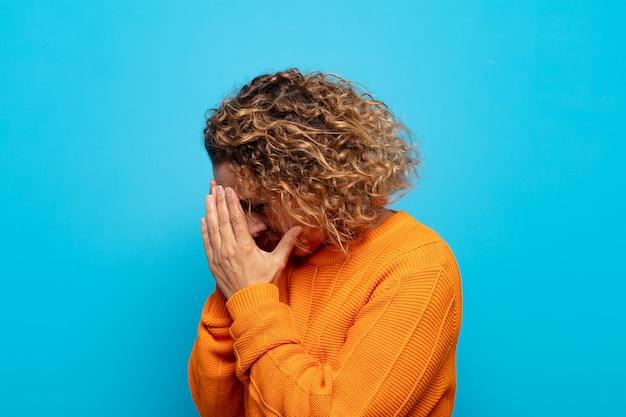 Mulher de meia-idade cobrindo os olhos com as mãos com um olhar triste e frustrado de desespero, chorando, vista lateral
