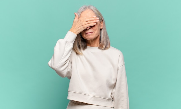 Mulher de meia-idade cobrindo os olhos com uma das mãos, sentindo-se assustada ou ansiosa, pensando ou esperando cegamente por uma surpresa