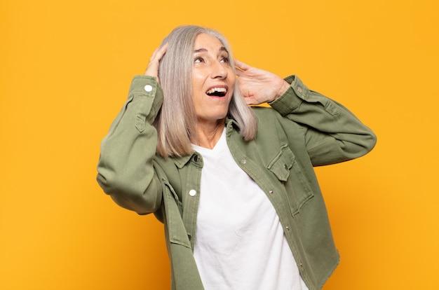 Mulher de meia-idade com a boca aberta, parecendo horrorizada e chocada por causa de um erro terrível, levando as mãos à cabeça