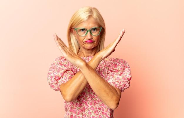 Mulher de meia idade com aparência impaciente e zangada, apontando para o relógio, pedindo pontualidade, quer ser pontual