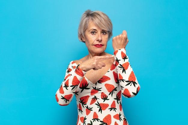 Mulher de meia-idade com aparência impaciente e zangada, apontando para o relógio, pedindo pontualidade, quer ser pontual