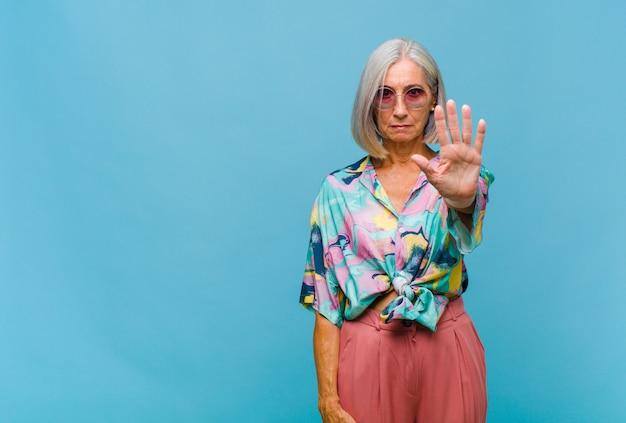 Mulher de meia-idade com aparência séria, severa, descontente e irritada mostrando a palma da mão aberta fazendo gesto de pare
