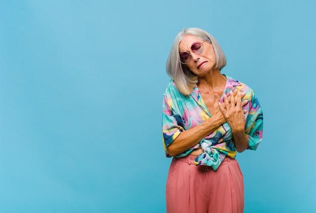 Mulher de meia-idade com aparência triste, magoada e com o coração partido, segurando as duas mãos perto do coração, chorando e se sentindo deprimida
