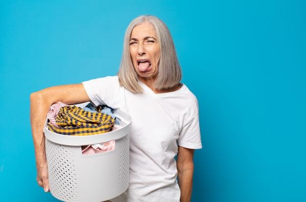 Mulher de meia-idade com atitude alegre, despreocupada e rebelde, brincando e mostrando a língua, se divertindo