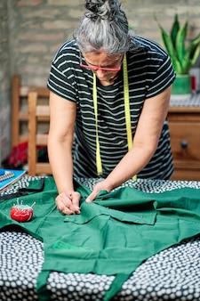 Mulher de meia-idade com cabelos brancos, usando óculos e fita de costura no pescoço, trabalhando na mesa de costura em casa.