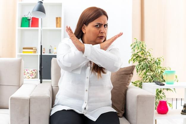 Mulher de meia-idade com camisa branca e calça preta com rosto sério e carrancudo, fazendo gesto de parada, cruzando as mãos, sentado na cadeira na sala iluminada