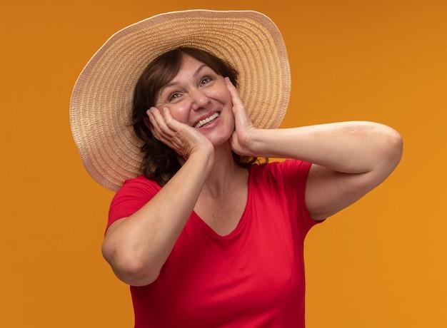 Mulher de meia-idade com camiseta vermelha e chapéu de verão olhando para o lado com uma cara feliz com as mãos nas bochechas em pé sobre a parede laranja
