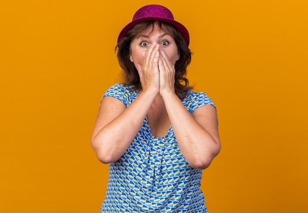 Mulher de meia-idade com chapéu de festa chocada cobrindo a boca com as mãos, comemorando a festa de aniversário em pé sobre a parede laranja