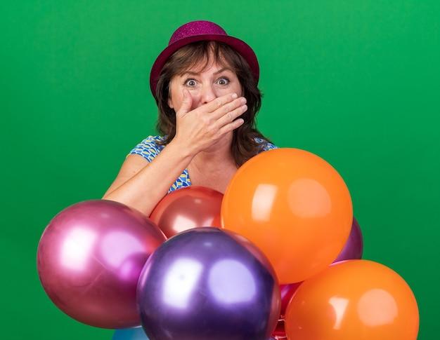 Mulher de meia-idade com chapéu de festa com balões coloridos espantada cobrindo a boca com a mão, comemorando a festa de aniversário em pé sobre a parede verde