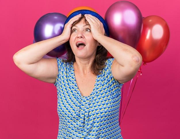 Mulher de meia-idade com chapéu de festa com balões coloridos, olhando feliz e animada com as mãos na cabeça