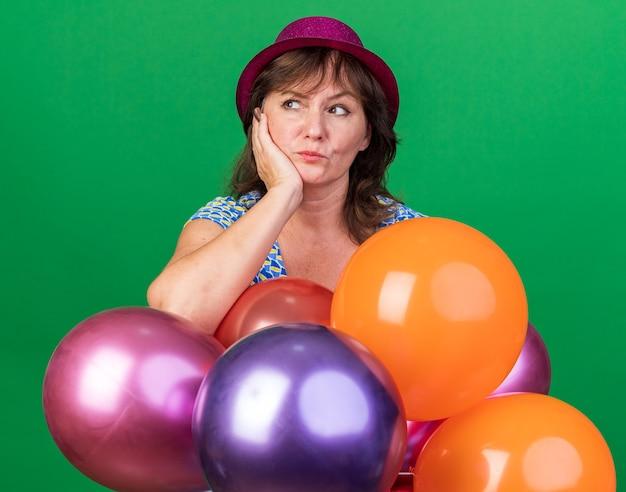 Mulher de meia-idade com chapéu de festa com balões coloridos olhando para o lado com expressão pensativa e pensando, comemorando a festa de aniversário em pé sobre a parede rosa