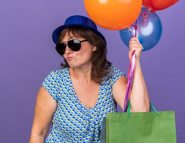 Mulher de meia-idade com chapéu de festa e óculos segurando um monte de balões coloridos e sacolas de papel com presentes parecendo confusa e descontente, comemorando a festa de aniversário em pé sobre a parede roxa