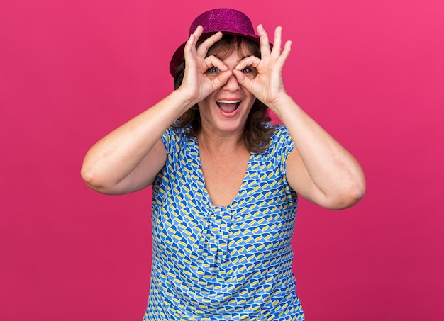 Mulher de meia-idade com chapéu de festa entre os dedos fazendo gesto binocular sorrindo alegremente