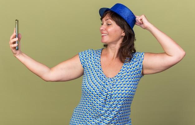 Mulher de meia-idade com chapéu de festa fazendo selfie usando smartphone feliz e positiva sorrindo alegremente