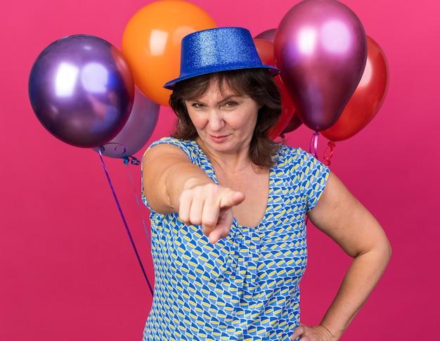 Mulher de meia-idade com chapéu de festa segurando balões coloridos apontando com o dedo indicador apontando