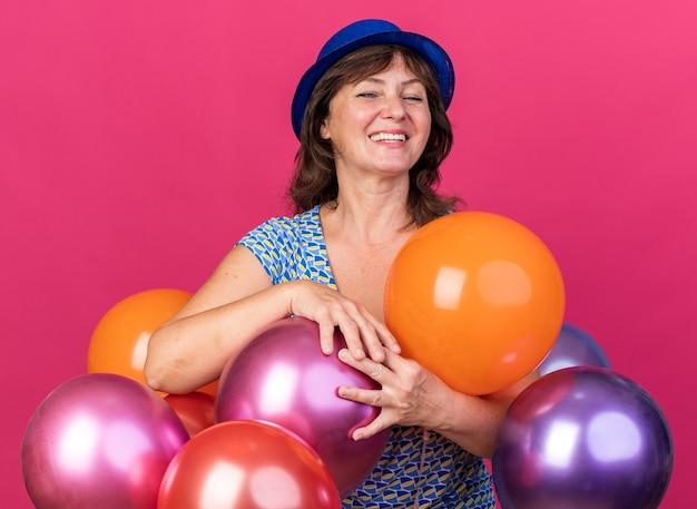 Mulher de meia-idade com chapéu de festa segurando balões coloridos e sorrindo alegremente