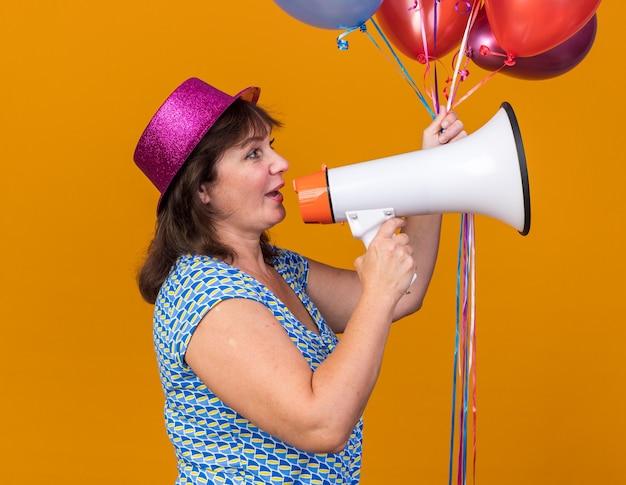 Mulher de meia-idade com chapéu de festa segurando balões coloridos gritando para o megafone feliz e positiva