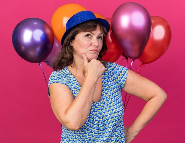Mulher de meia-idade com chapéu de festa segurando balões coloridos, olhando para cima com expressão pensativa e pensando