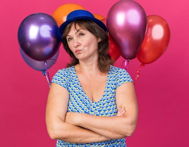 Mulher de meia-idade com chapéu de festa segurando balões coloridos olhando para o lado com expressão pensativa e pensando com os braços cruzados