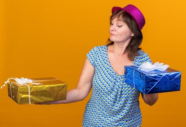 Mulher de meia-idade com chapéu de festa segurando presentes de aniversário, parecendo confusa e com dúvidas