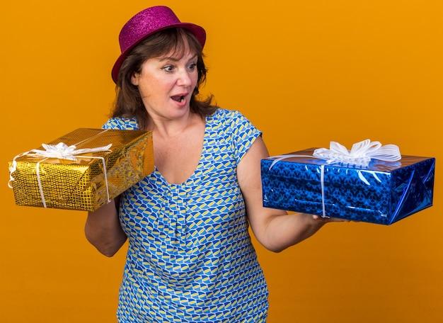 Mulher de meia-idade com chapéu de festa segurando presentes de aniversário, parecendo surpresa e feliz